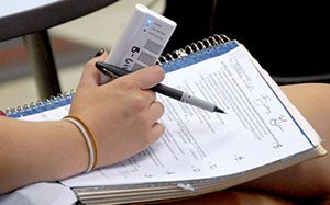 hand holding clicker and notebook